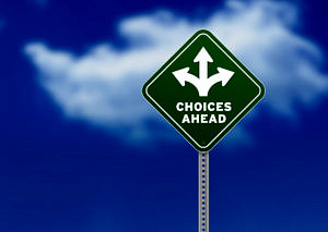 """Bild zeigt blauen Himmel mit Wolken. Davor sieht man ein dreieckiges Schild mit der Aufschrift """"Choices ahead"""""""